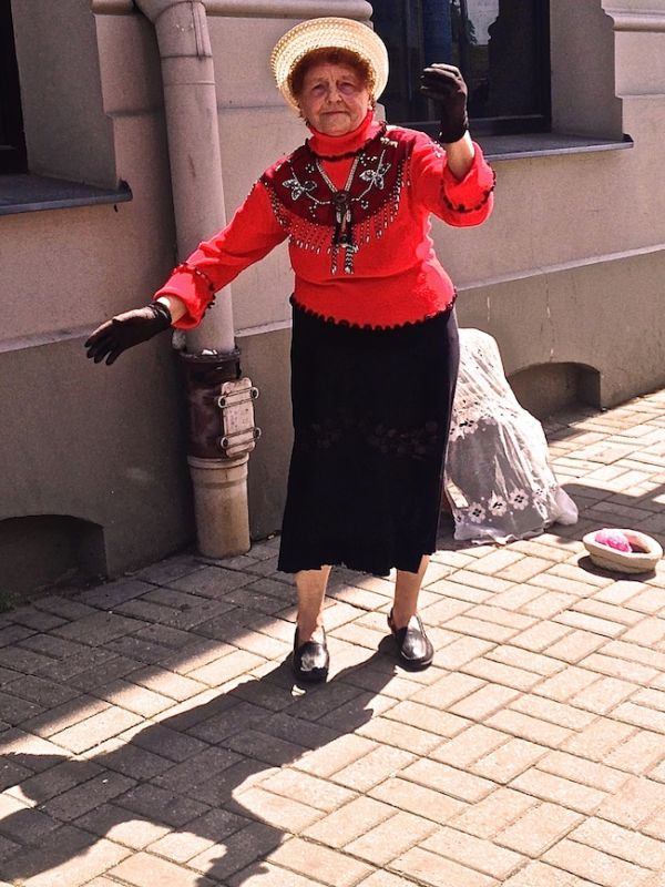 Old lady dancing street entertainer in Riga's Old Town
