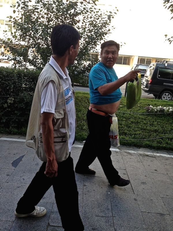 Man walking down Ulan Bator's streets with his top rolled up