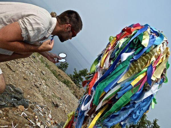 Seb fait une offrande en nature au totem sacré de cap Khoboi sur l'île d'Olkhon