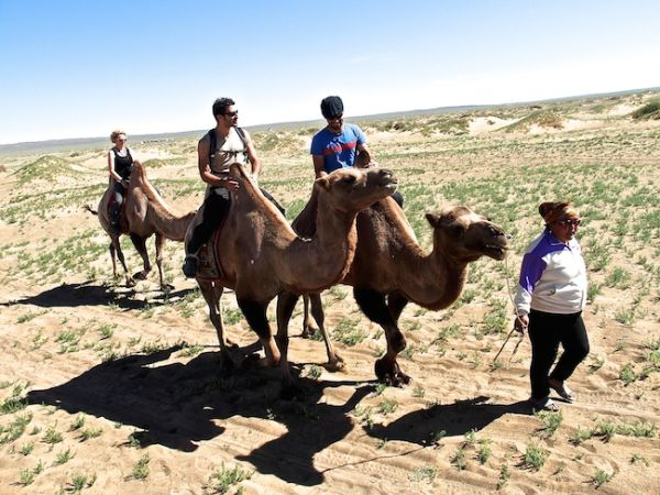 Posing and riding our camels through the Gobi desert at Khongoryn Els
