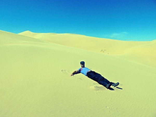 Seb essaie de faire un ange de sable avec ses mains et ses pieds