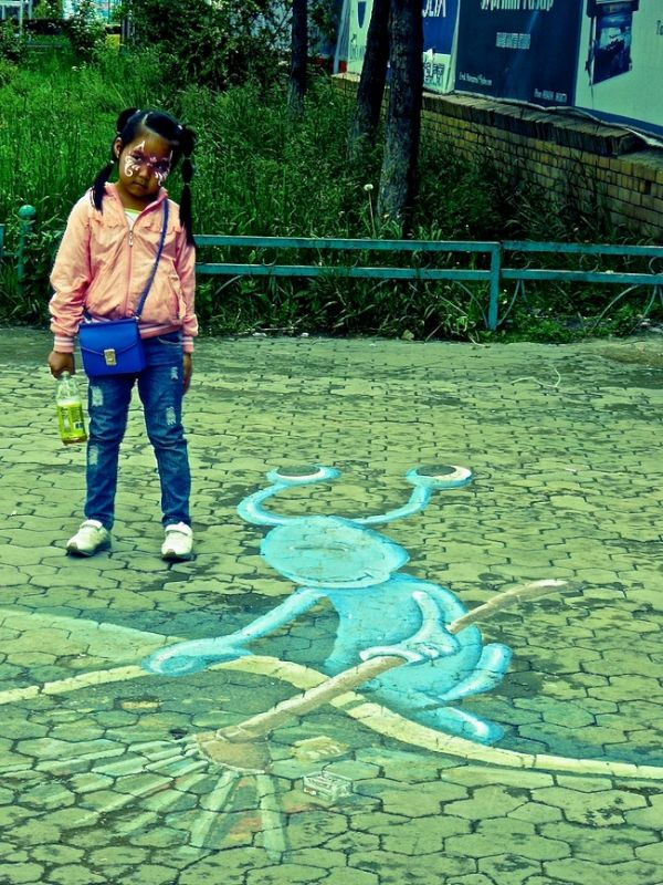 Little girl posing on a 3D pavement graffiti in Ulan Bator