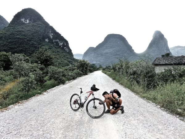 Checking bike whilst cycling in Yangshuo