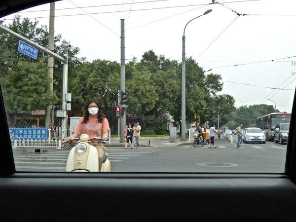 Chinois en scooter portent un masque, à Pékin en Chine