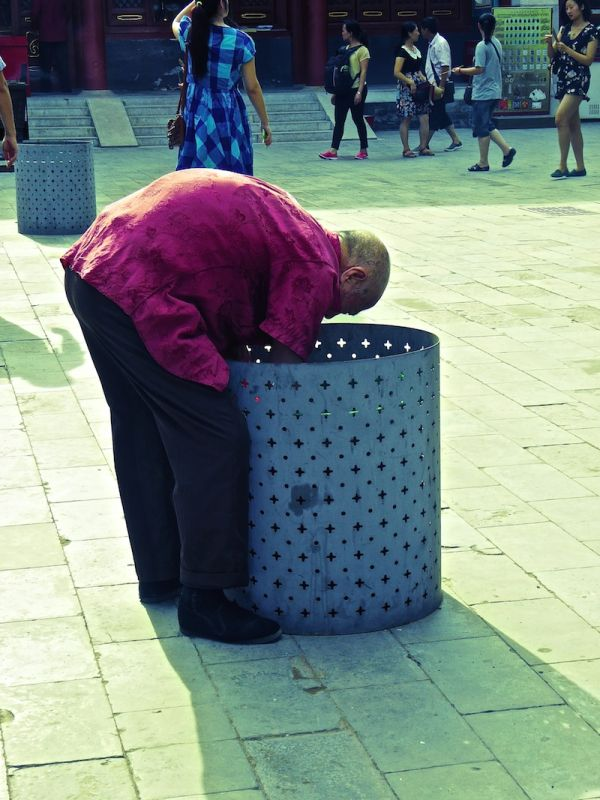 An old man searching for and collecting plastic bottles in Beijing's Lama Temple keeping the city clean