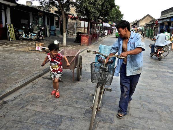 Un petit garçon et son père dans une rue de Pingyao