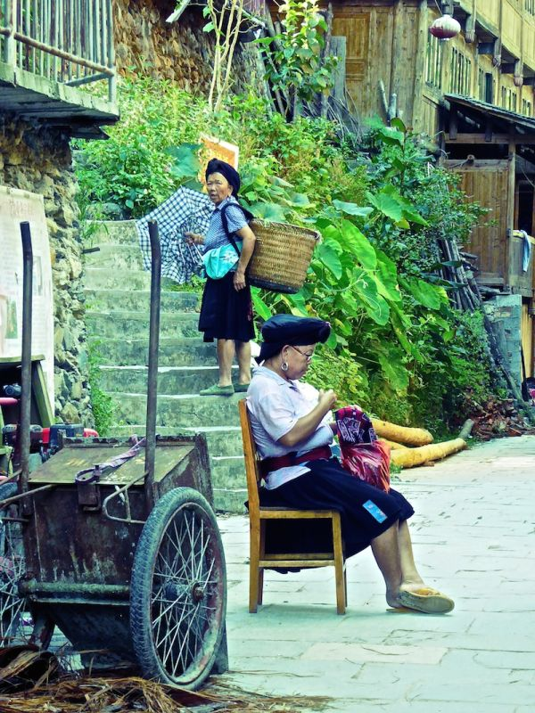 Old lady of Tiantouzhai village carrying bags up the Longji Rice Terraces