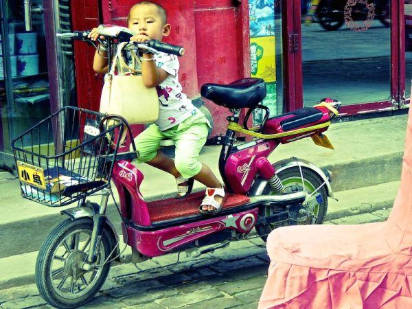 Scène de rue dans la vieille ville de Pingyao : un enfant sur son scooter