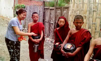 Nan Bwe of Yoe Yoe Lay Guesthouse offering food to the monks