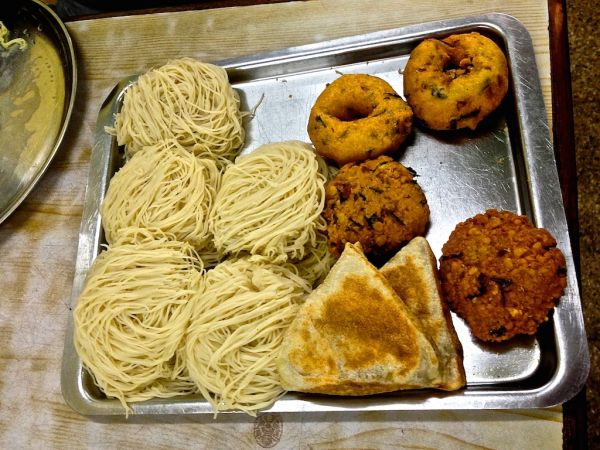 A plate of string hoppers, vegetable rotis and various vadai (lentils based) snacks