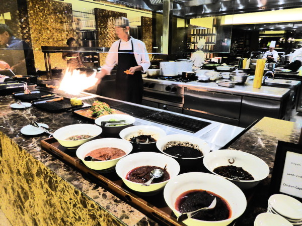 Chef cooking in open kitchen at Tanjun Ria at the Hyatt
