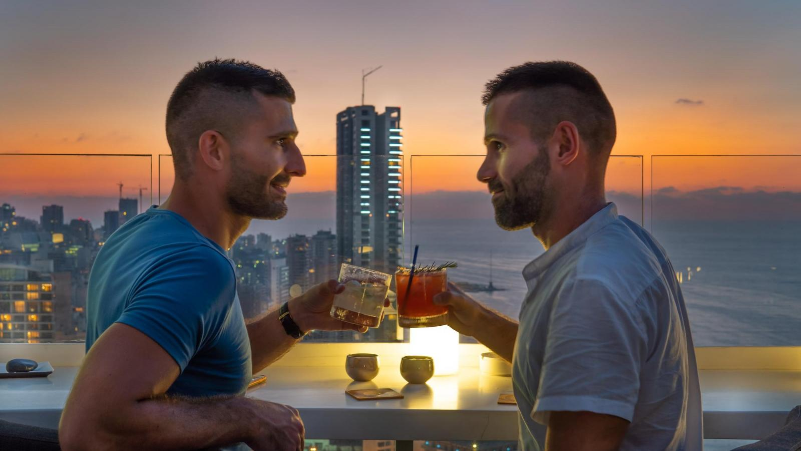 Gay couple in Beirut enjoying a cocktail at the rooftop bar of the Four Seasons Hotel