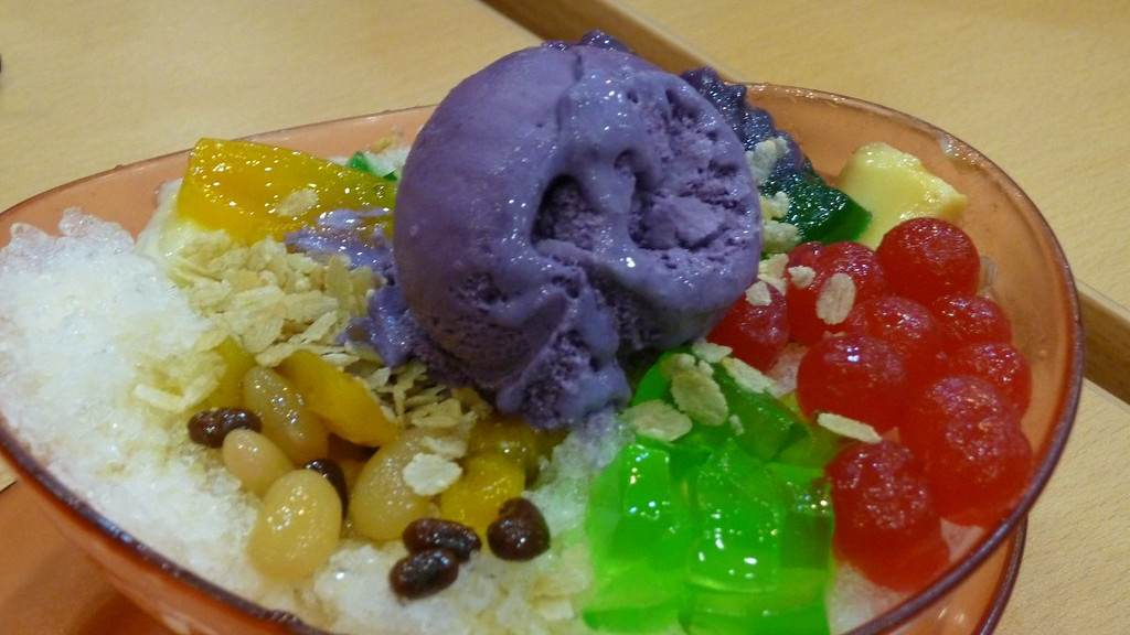 Halo Halo Filipino desert presented in a transparent dish with ice creams and beans