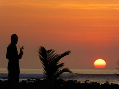 Gay travel to Bali - the sunsets in Bali are incredible, grab a cocktail and watch it with your partner on the beach