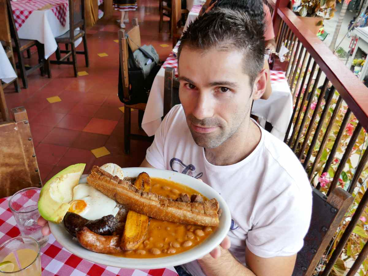 Seby from Nomadic Boys holding a plate of Bandeja Paisa in Medellin, Colombia