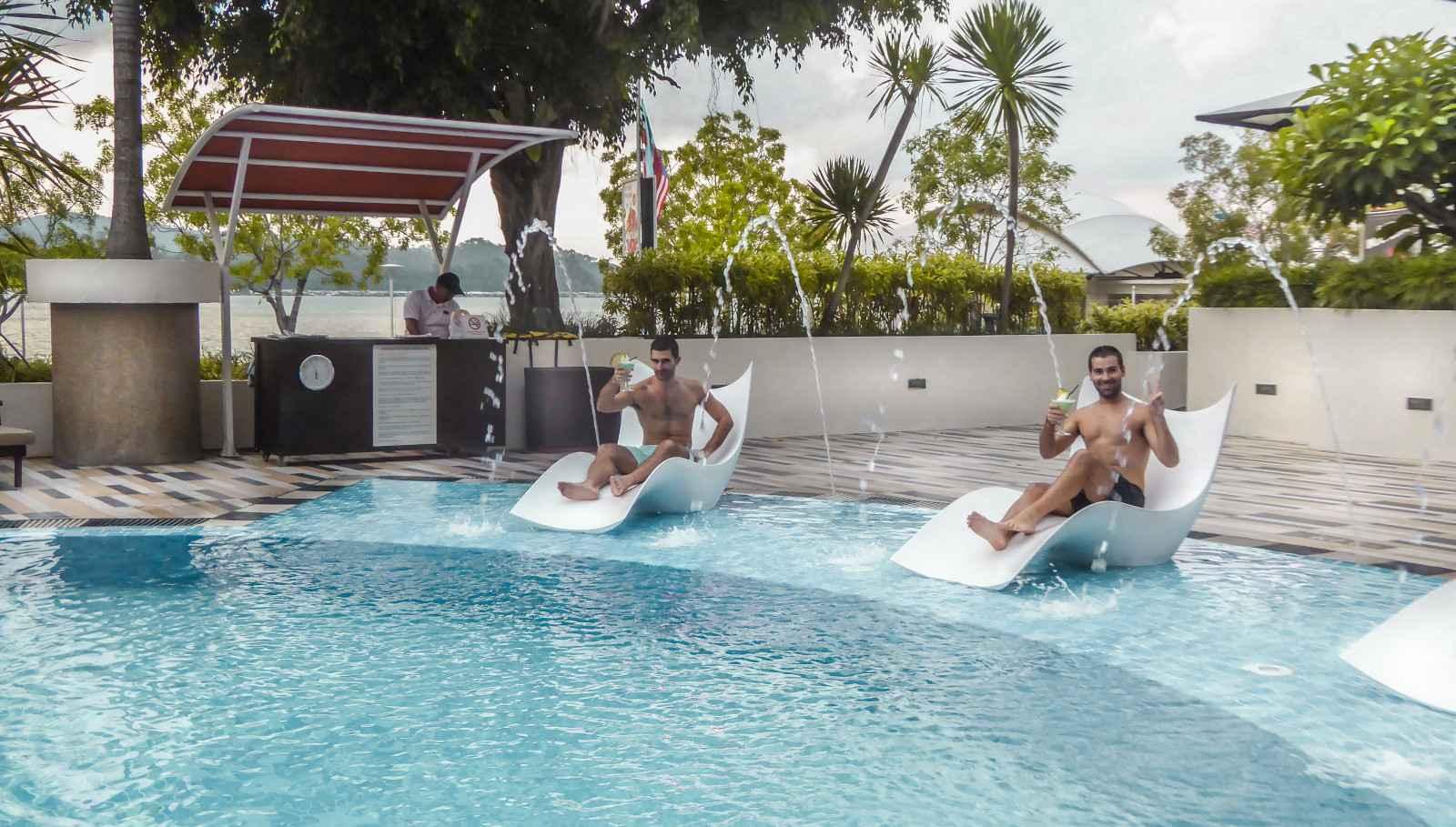 Meninos nômades relaxando à beira da piscina do hotel gay friendly Regency Gyatt em Kota Kinabalu