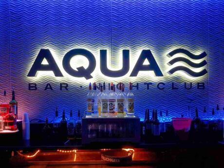 Aqua gay bar illuminated in a dark background in Key West