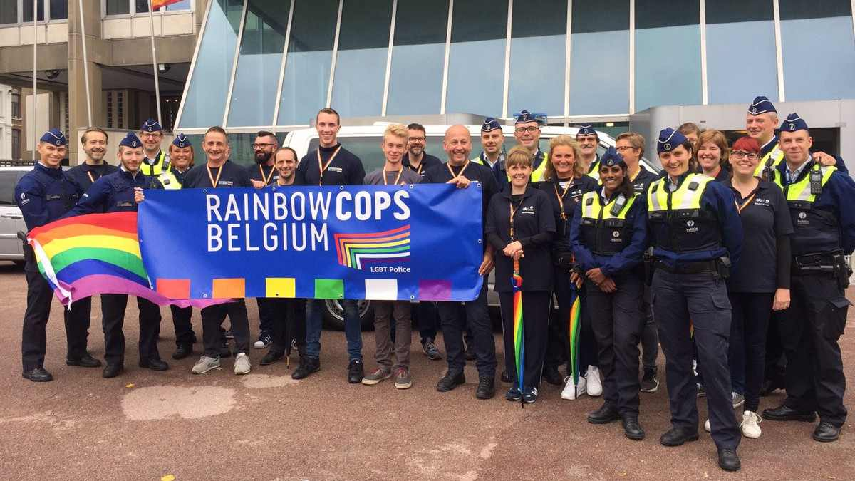The rainbow cops team of Belgium posing with the rainbow flag